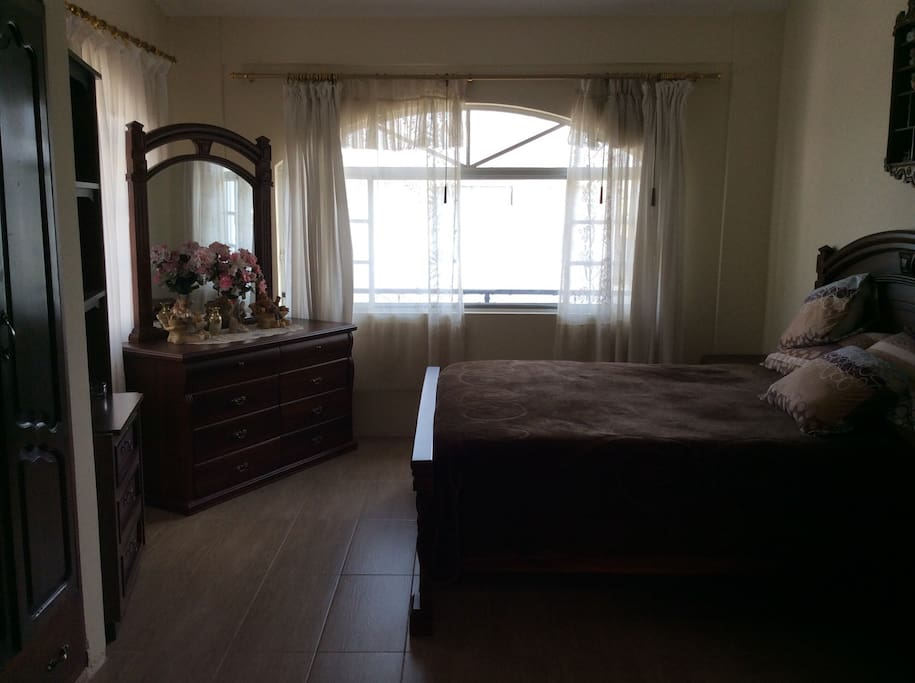 This is the bedroom with a queen size bed with two night tables on each side, a bureau, and spacious wardrobe, and ensuite bathroom.