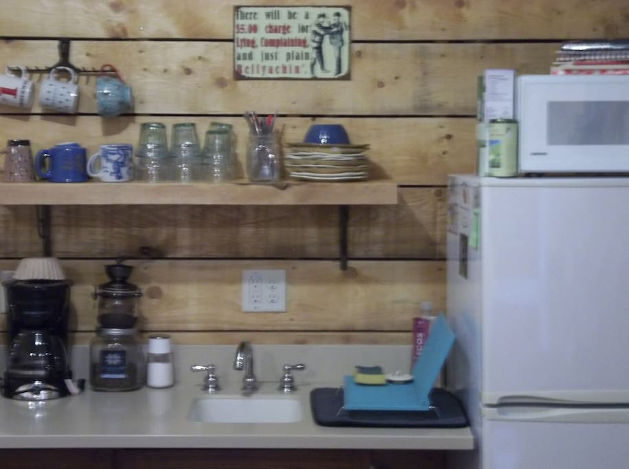 The primitive kitchenette has a hot plate, microwave, toaster, fridge & freezer and sink.
