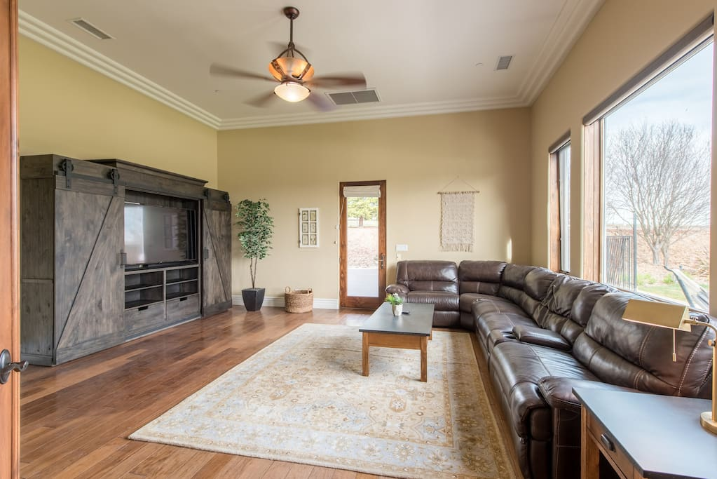 """Upscale theater room with 65"""" TV and leather sectional sofa."""