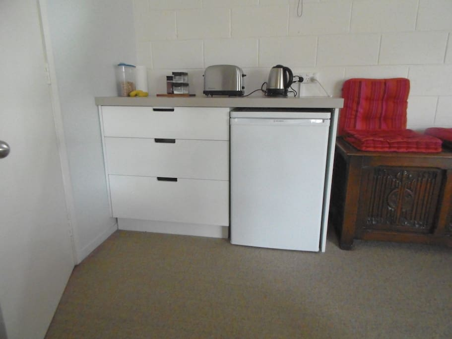 Kitchen unit with fridge under, jug microwave and toaster.