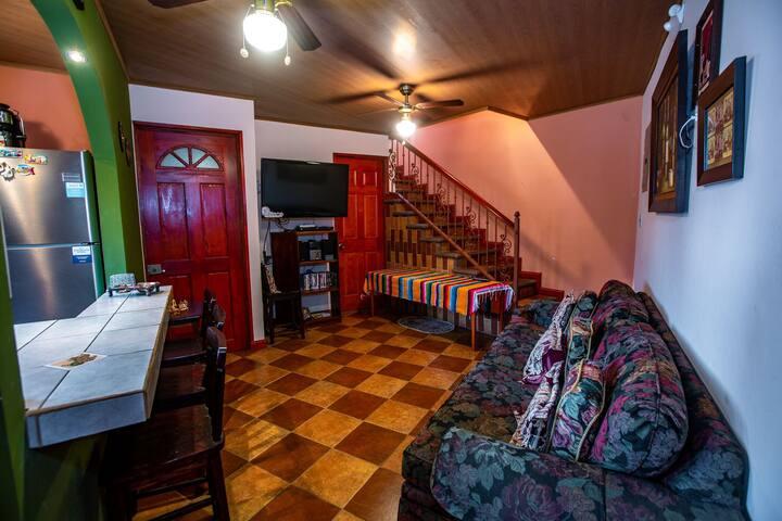 Amplia sala con sofá cama acceso a baño y escalera a salón de juegos