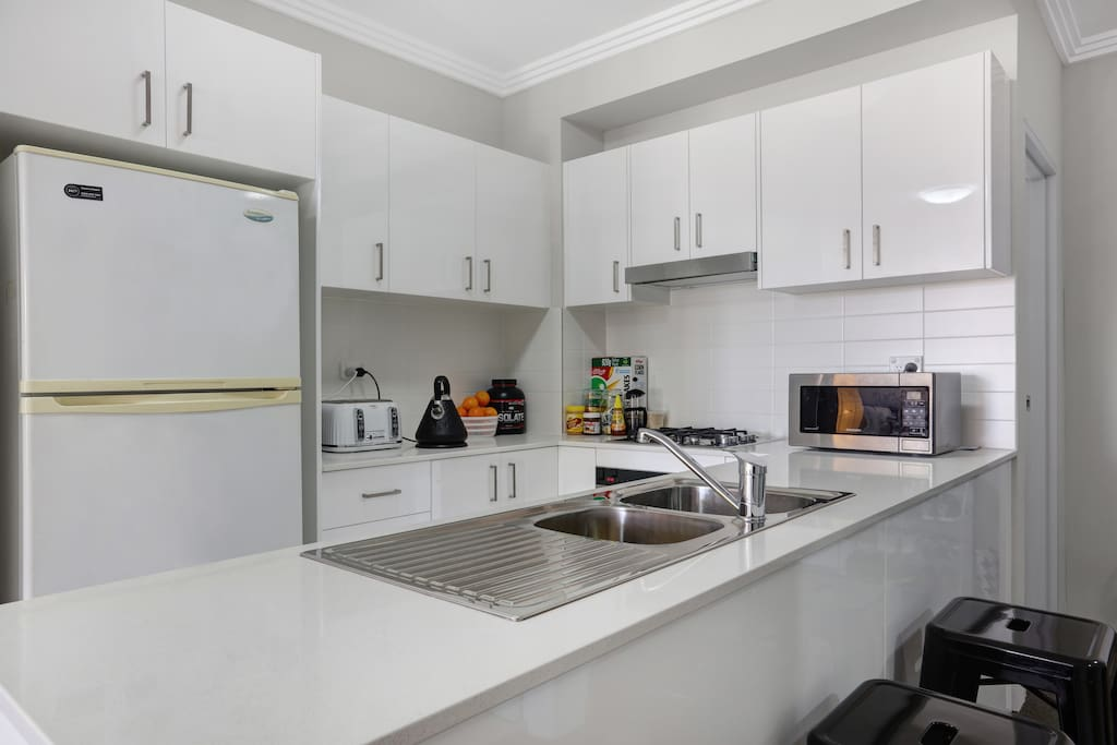 Modern kitchen with stone benchtops,gas cooking appliances,microwave and dishwashe