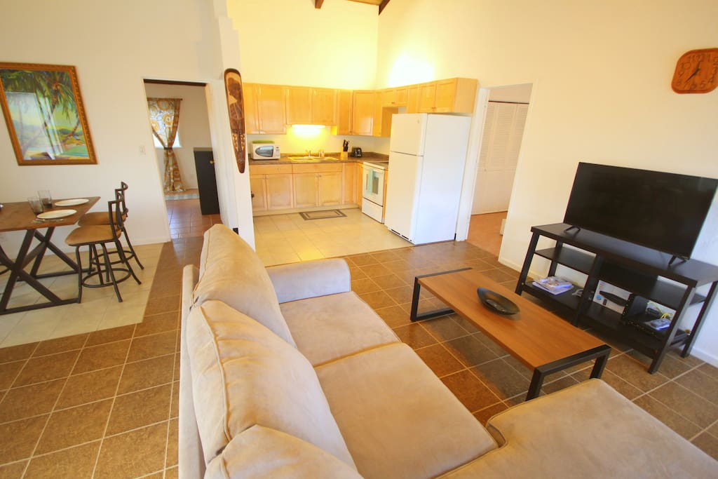 There is a full kitchen, dining area, and a living area with flat screen TV and comfortable couch.