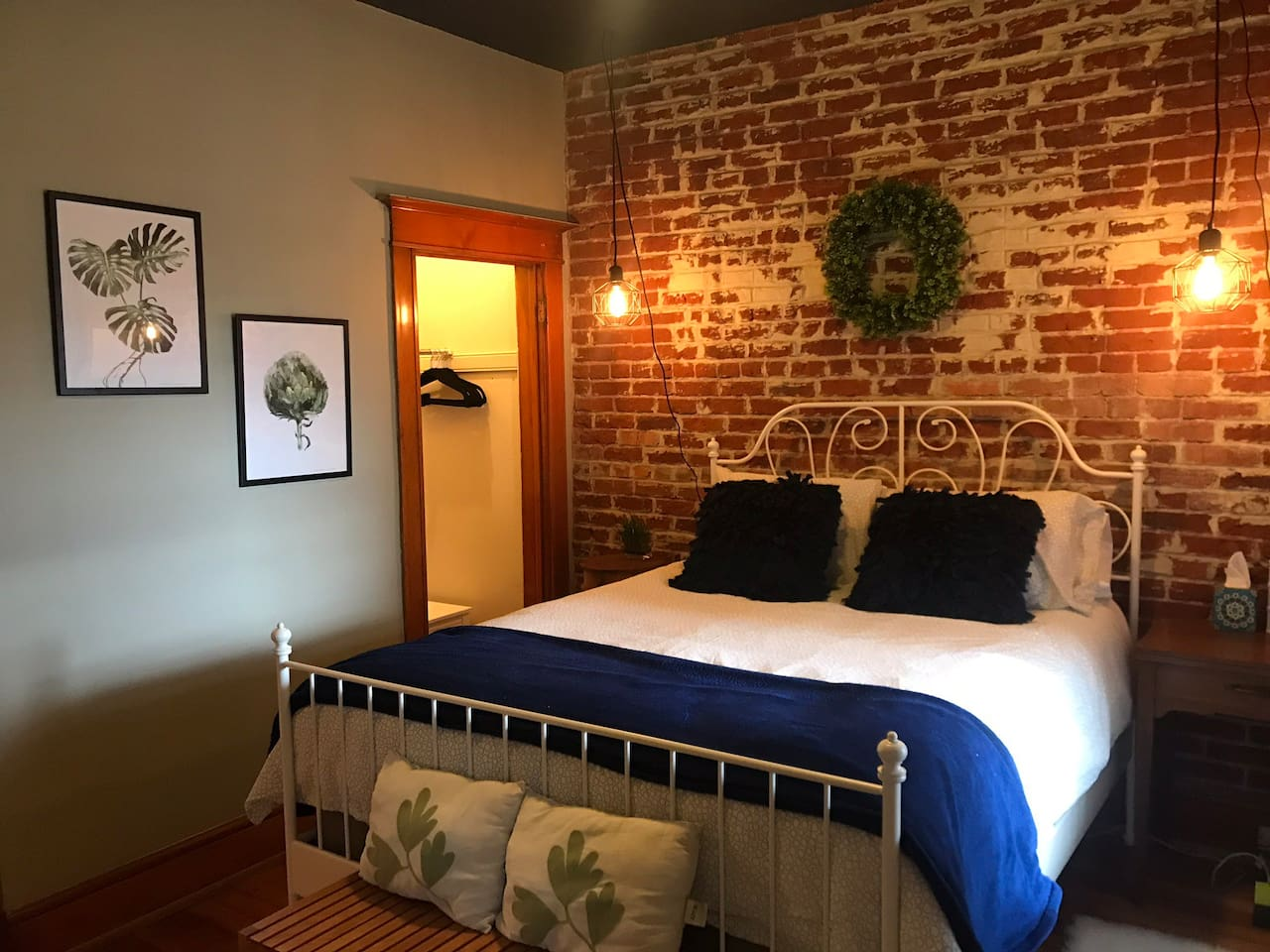 Your private room with organic cotton sheets, cozy blankets and exposed brick.