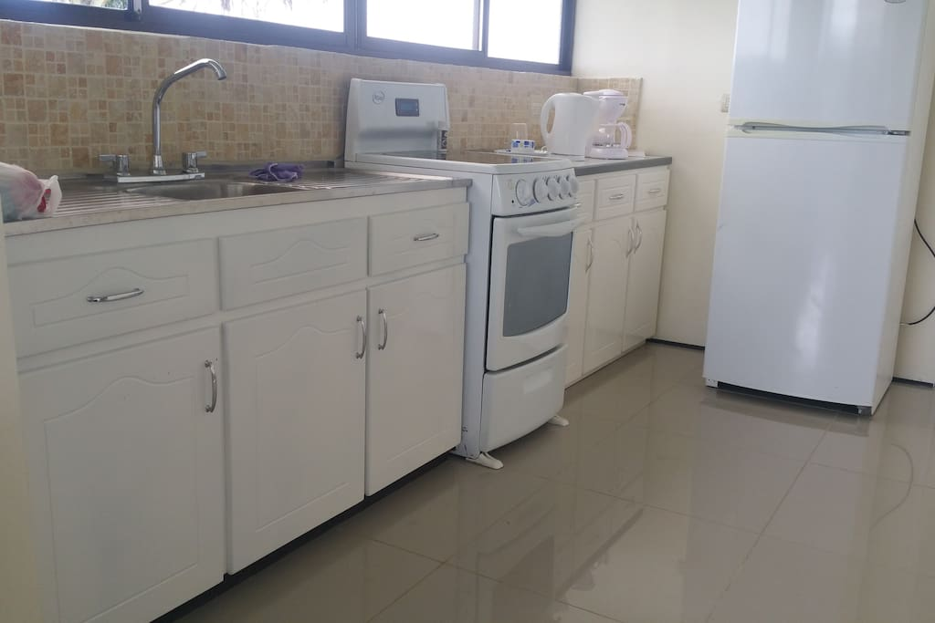 Kitchen with fridge, stove, microwave, toaster, coffee maker, kettle, and all utensils.