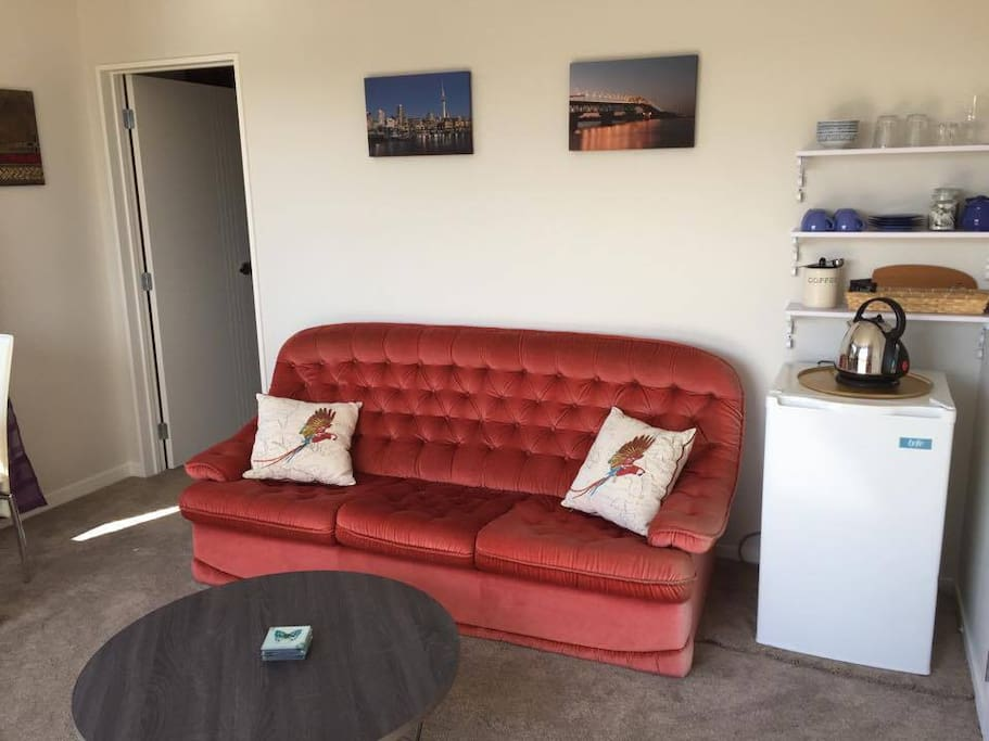 Lounge with sofa, coffee table, small dining table, TV, DVD player and fridge