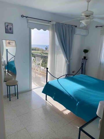Спальня с большой двуспальной кроватью , с выходом на веранду и видом на море и закат .