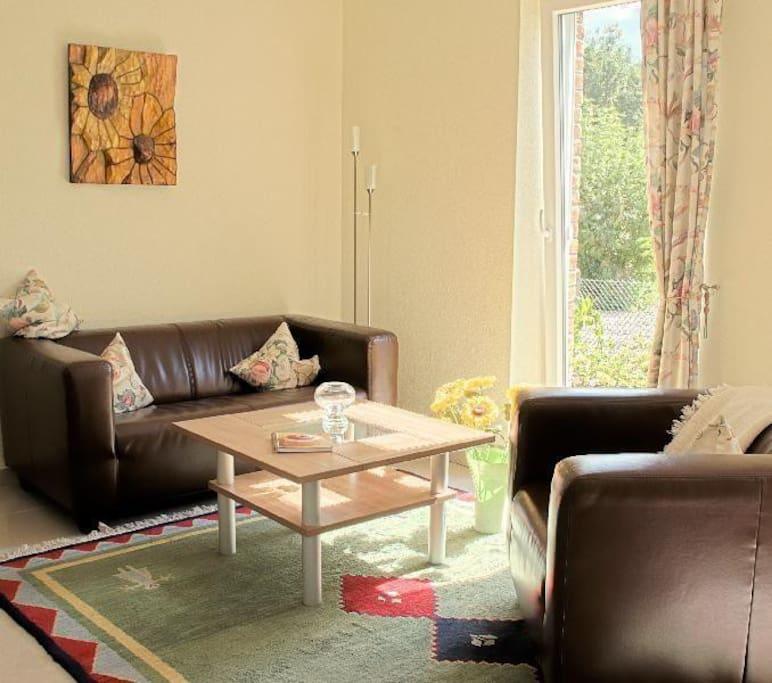 Gemütlich geschmackvoller Wohnbereich mit drei großen Terrassenfenstern in Süd-West-Ausrichtung