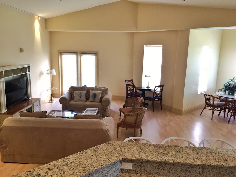 Open great room  with flat screen, multiple sitting areas, a breakfast nook, and French doors that lead to a private balcony.