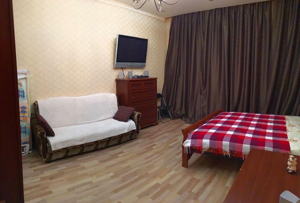 Гостиная-Спальня: кровать (160 см ширина), диван, окно за шторой, телевизор, прикроватный столик, гладильная доска