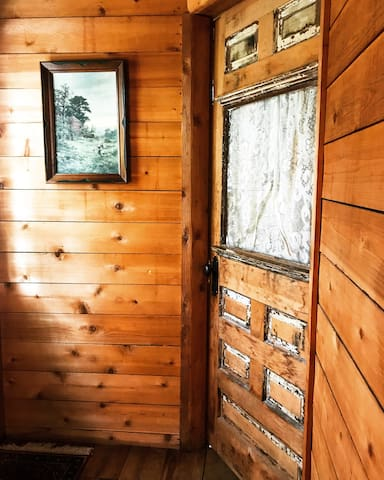 Antique door with beautifully chipped paint leading to the bathroom.