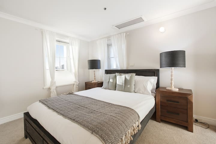 Down on the first floor you'll find a sun-soaked second bedroom with a queen bed dressed in high-quality linen and sleek timber furnishings