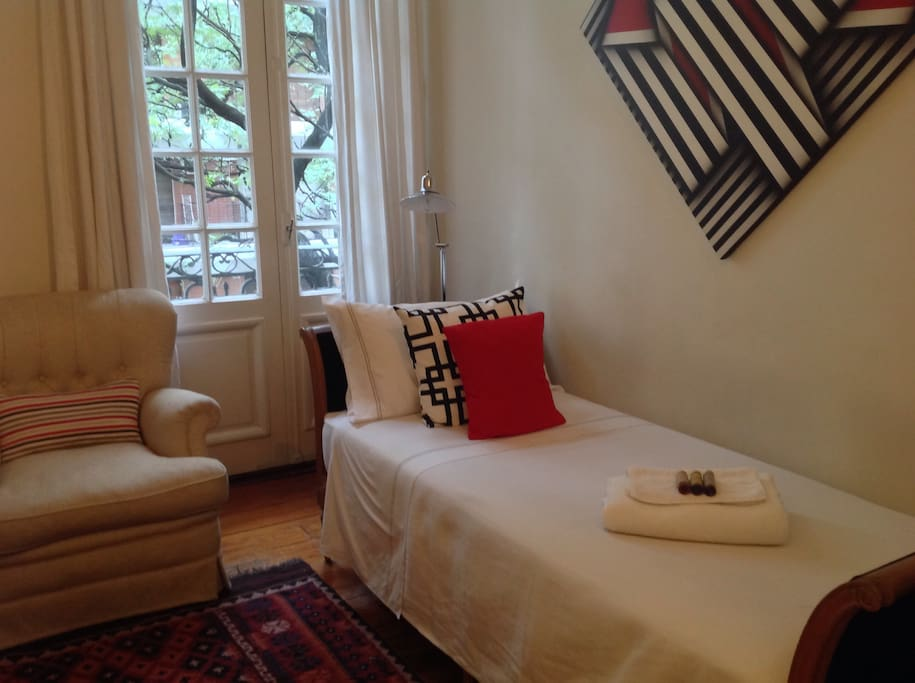 The guest bedroom overlooking the street with impecable linen and feather pillows