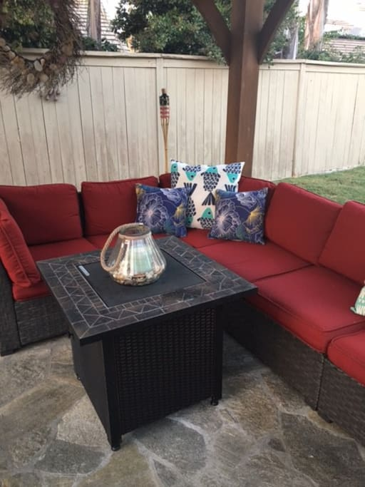 firepit and couch sitting under gazebo, 4 extra chairs as well