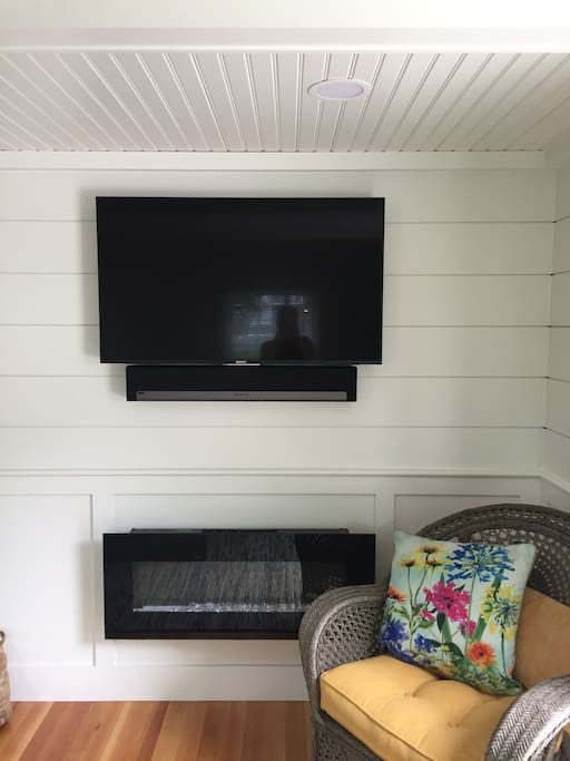 Flat screen with Sonos sound bar and electric fireplace.