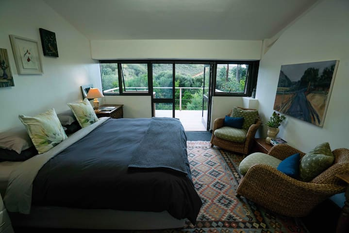 Bedroom with king size bed and door leading to balcony.