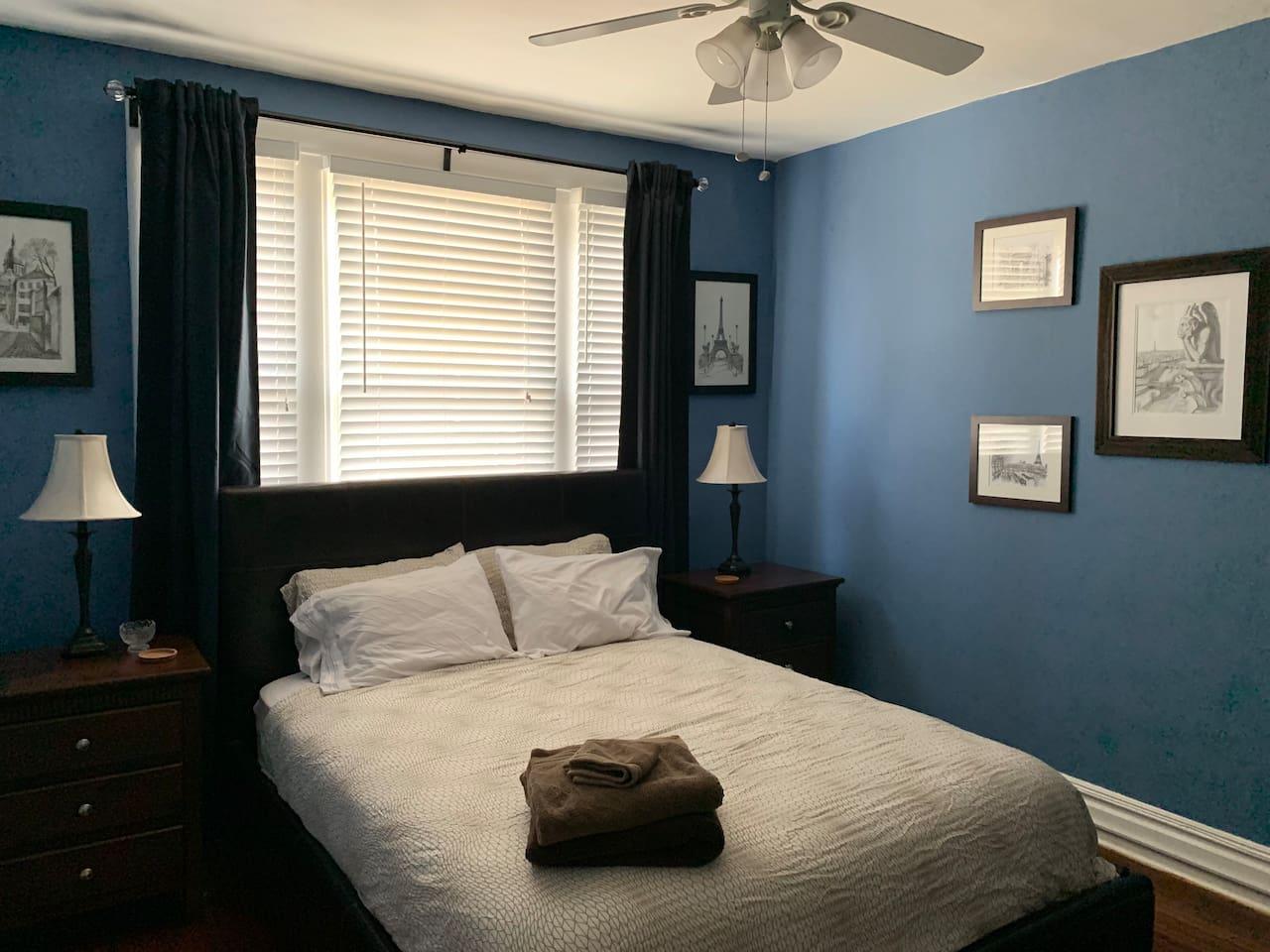 Blue bedroom has queen size bed, dresser, nightstands and closet