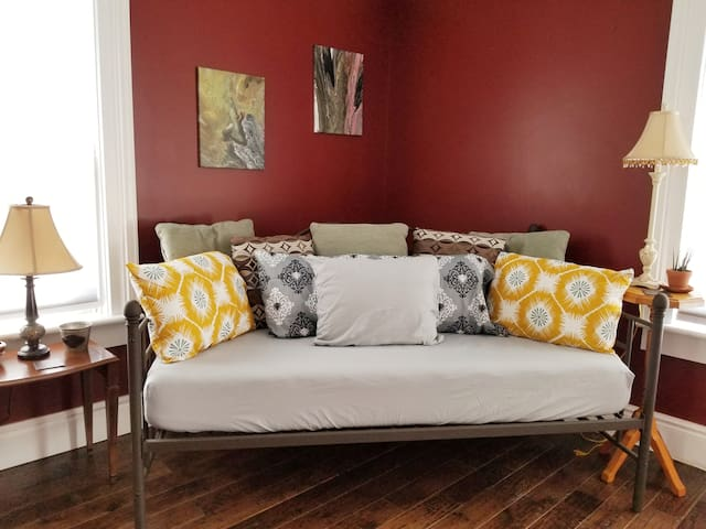 Living room with daybed. Comfy cushions on a medium firm memory foam mattress. Windows in this area have pull down blinds for privacy.