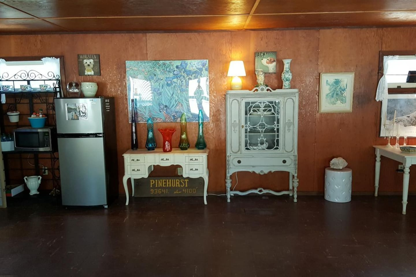 Art filled space with refrigerator, microwave, toaster oven, coffee maker, dishes and flatware.