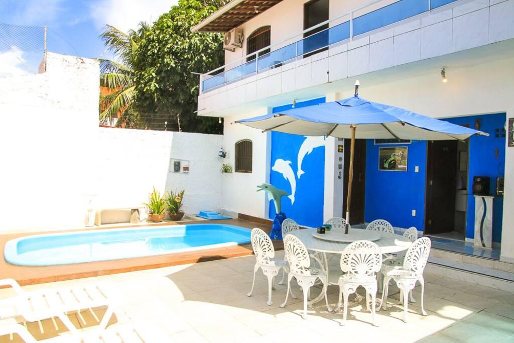 Área externa com piscina, churrasqueira, mesa, cadeiras, espreguiçadeiras e geladeiras disponíveis.