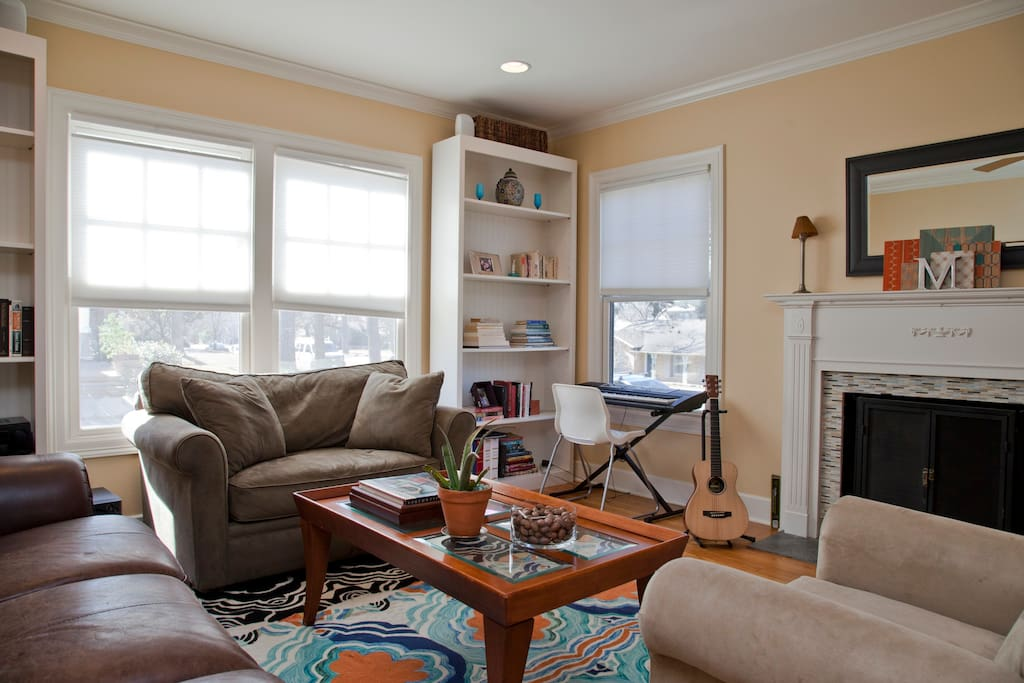 Spacious living room with wood-burning fire place and lots of great light.