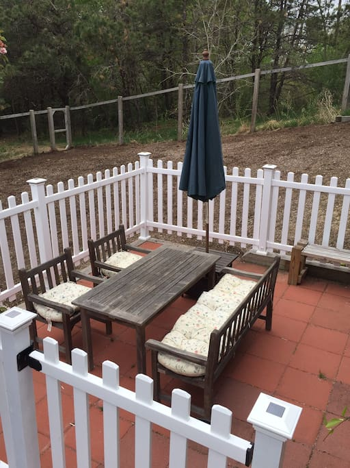 Teak table, chairs, umbrella, BBQ grill.