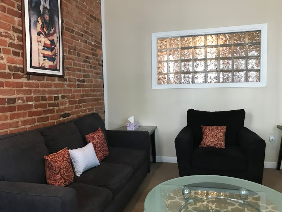 Exposed brick and glass bricks fill the room with character