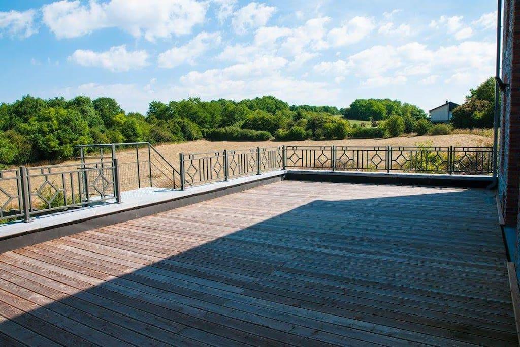Vaste terrasse sécurisée offrant un paysage champêtre et apaisant.