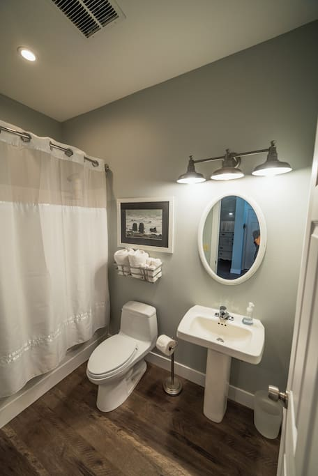 A clean, bright and simple private bathroom including a shower with deep tub.