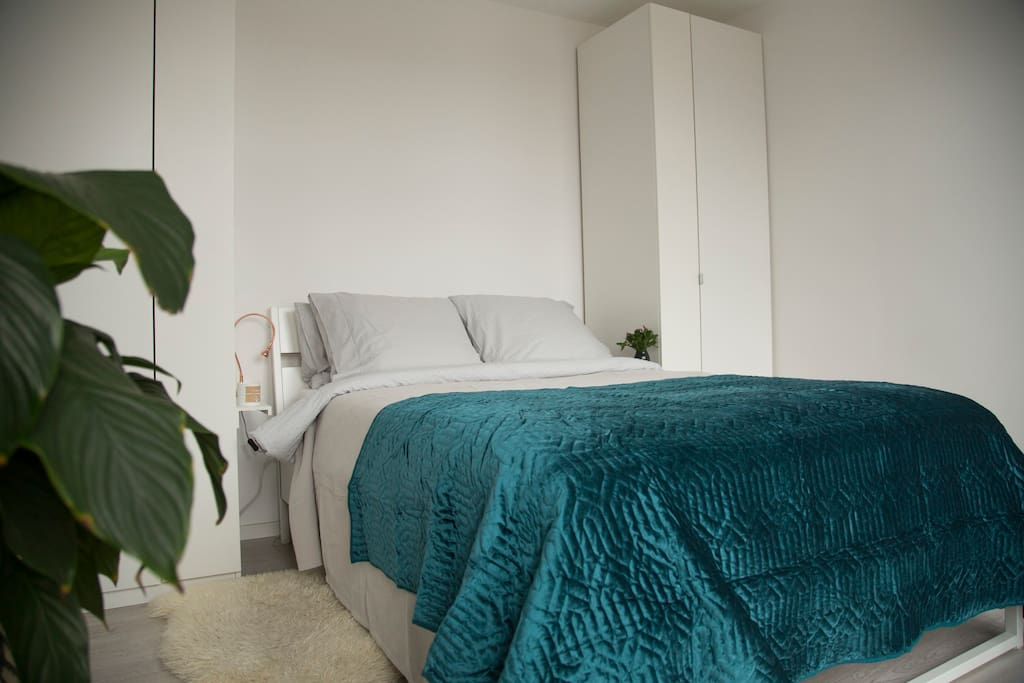 1st bedroom with a double bed and a French balcony overlooking the street.