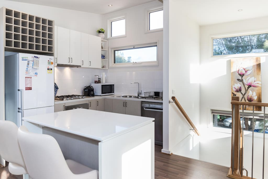 Modern kitchen with dishwasher, fridge, electric oven, gas cooktop, microwave, coffee machine and island bench