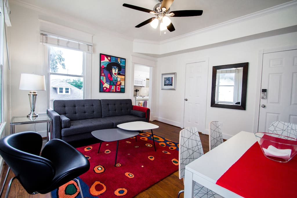 """Light filled open living room and Dining room with a 40"""" TV."""