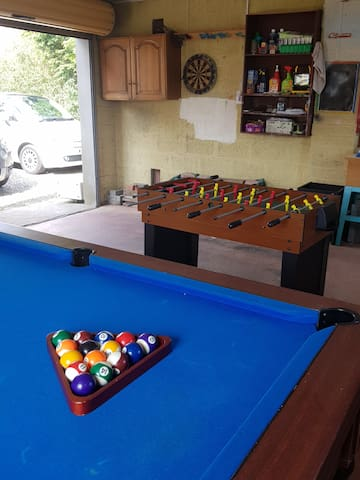 Games room in nearby garage with pub pool table darts and games table plus storage space for guests.