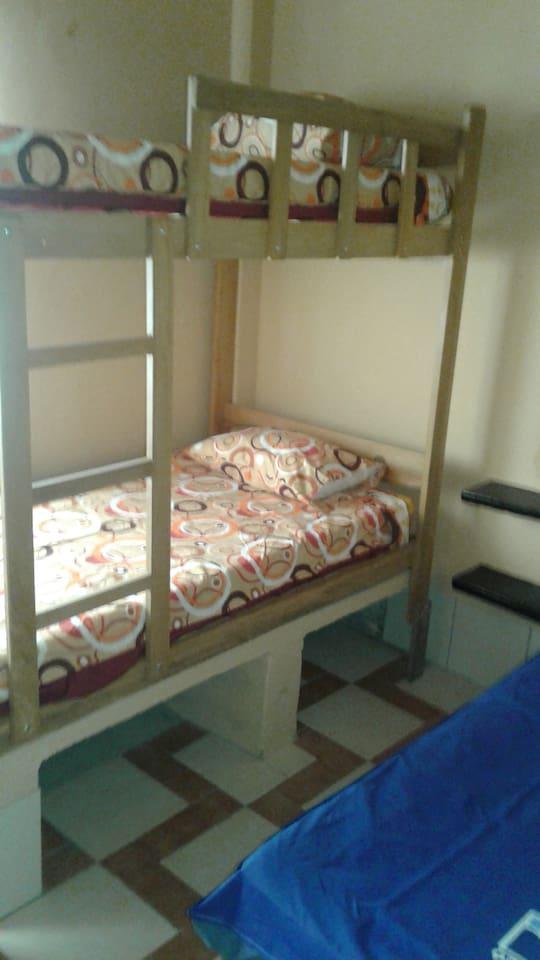 Habitaciòn 1 cama media plaza, 1 camarote con baño compartido.