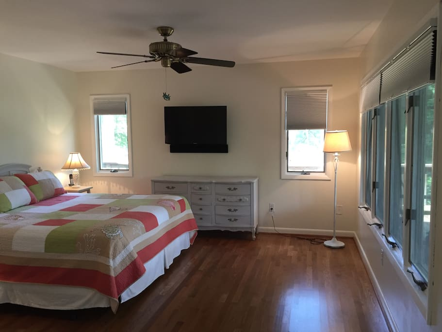 Master bedroom has a king-sized bed, view on two sides of Moore's Creek, attached screened-in porch, 40-inch TV and attached master bathroom.