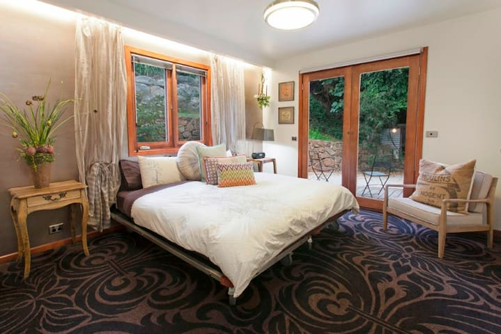 The carpeted ground floor bedroom has a king sized bed with two floor to ceiling windows overlooking the garden.