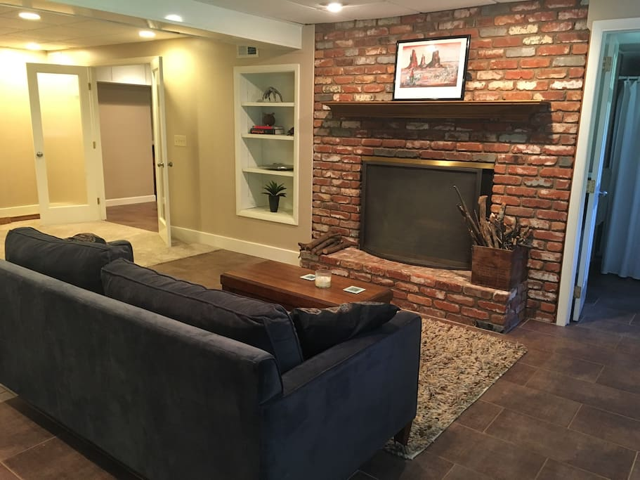 Wood burning fireplace. Cozy up on the modern velvet 6 foot couch(bring linens for 5th person to sleep on couch). Natural light from double hung windows. Bathroom is on right. French doors on left open to pool table, kitchen and dining area.