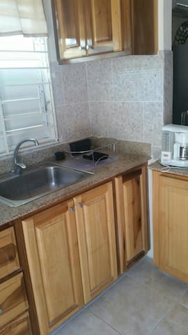Kitchen cabinetry with adequate storage. stocked with cooking utensils, crockery and drinkware. Two slice Toaster, coffee/ Tea maker and Blender can be found on the breakfast counter top.