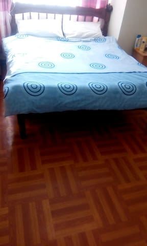spacious bedroom with a king size bed, spacious closet, polished wooden floors