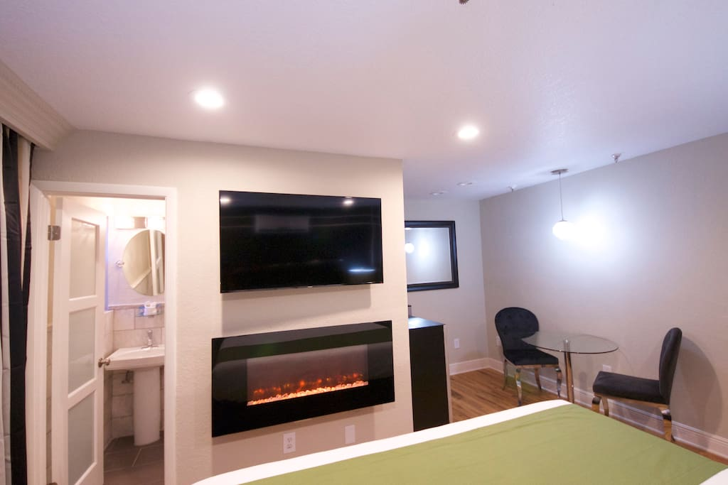 View of large flat screen television & wall mounted fireplace