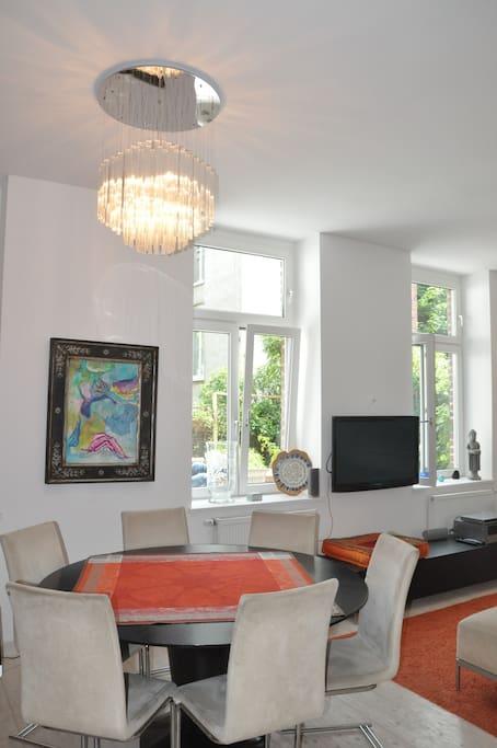 Wohnzimmer mit rundem Esstisch für bis 8 Leute
