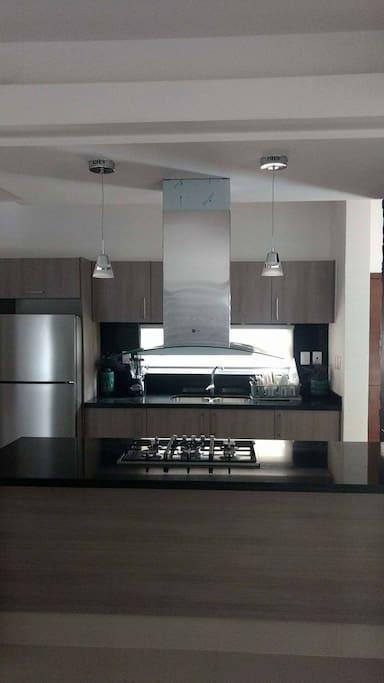 amplia cocina con todo,  licuadora horno microondas horno estufa refrigerador y utensilios para cocinar