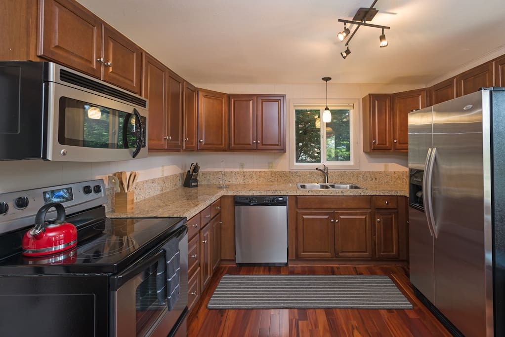 The spacious kitchen boasts hardwood floors, ample granite counter space, and stainless steel appliances.