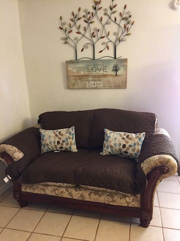 The living room and kitchen are open to each other.  There is a comfortable loveseat and sweet décor.  This is a great place to visit, leave the porch door open, barbecue on the grill outside.  There is so much restful potential.