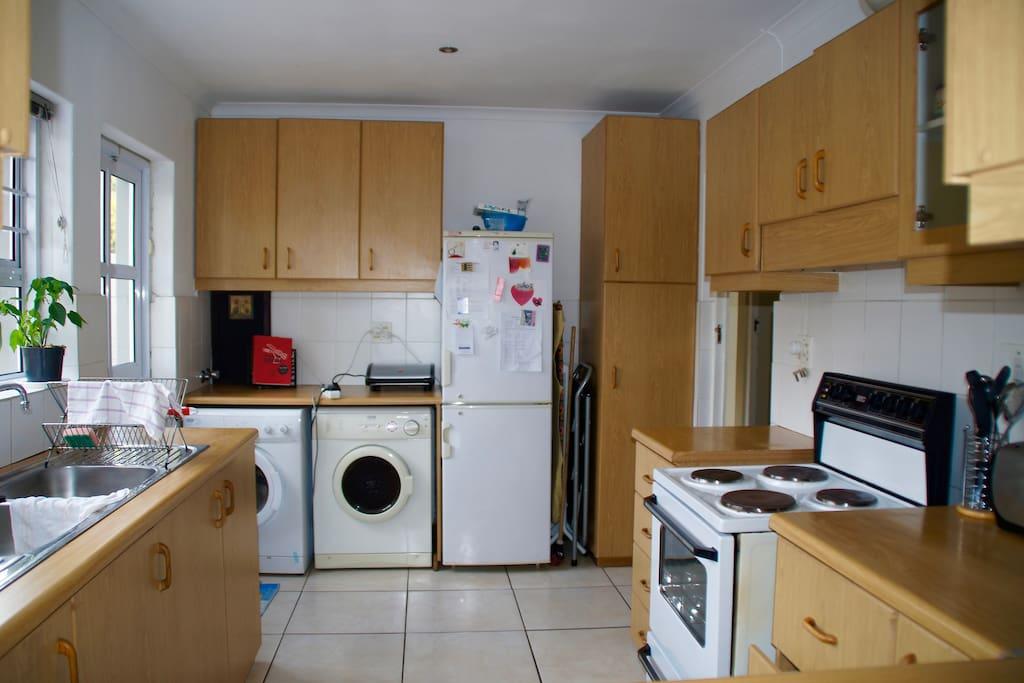 Kitchen with fridge, washing machine and dryer