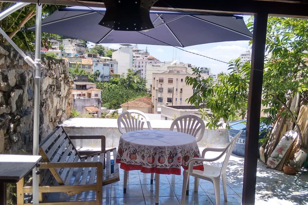 Vista, mesa com cadeiras, bancos e guarda sol.
