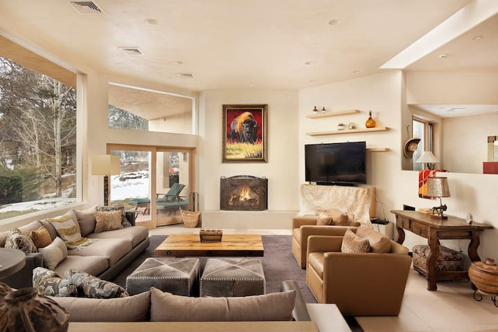 Spacious, gorgeous living room with a large fireplace and unbelievable views of Mount Sopris from floor to ceiling windows.