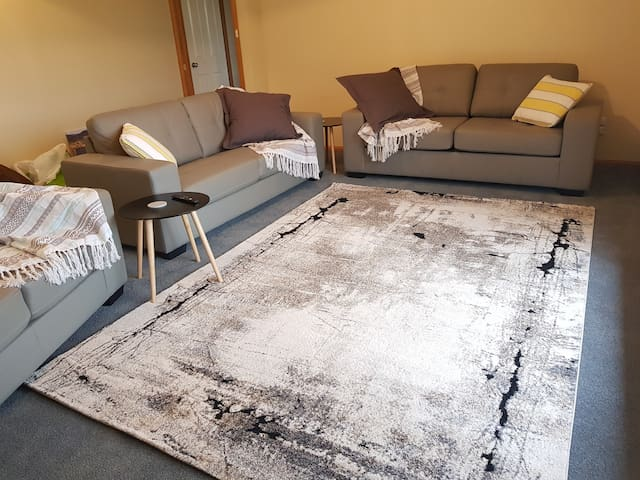 Spacious lounge room with a 2 seater and a 3 seater couch, plus a 3 seater sofa bed which opens out to a double bed.