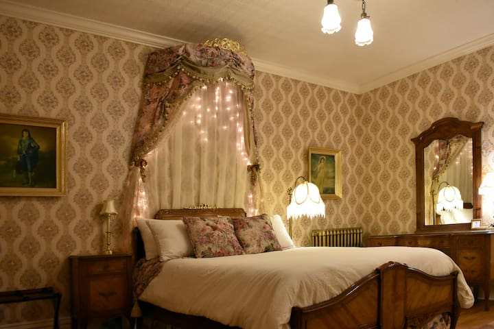 Beautiful room paying homage to true Victorian tastes with its circle canopy and tasseled drapes.  This firm antique full bed has soft cotton sheets.