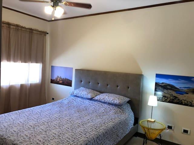Espacio dormitorio con cama queen